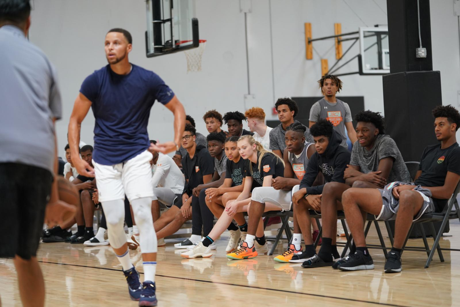 Azzi Fudd and Cameron Brink look on as Stephen Curry holds court at the SC30 Select Camp