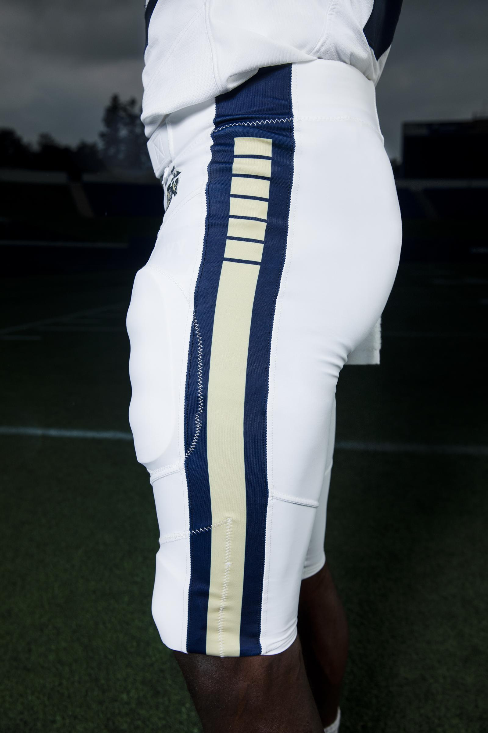 To match the jersey, the pants were designed in the same shade of navy blue with a stripe down the panel featuring six breaks. This same design is echoed on the helmet, since the United States Navy was founded by Congress with six frigates.  The one consistent element that this uniform shares with Navy's current standard uniforms is the Eagle, Globe and Anchor, the official emblem and insignia of the United States Marine Corps, which is seen on the pant hip.
