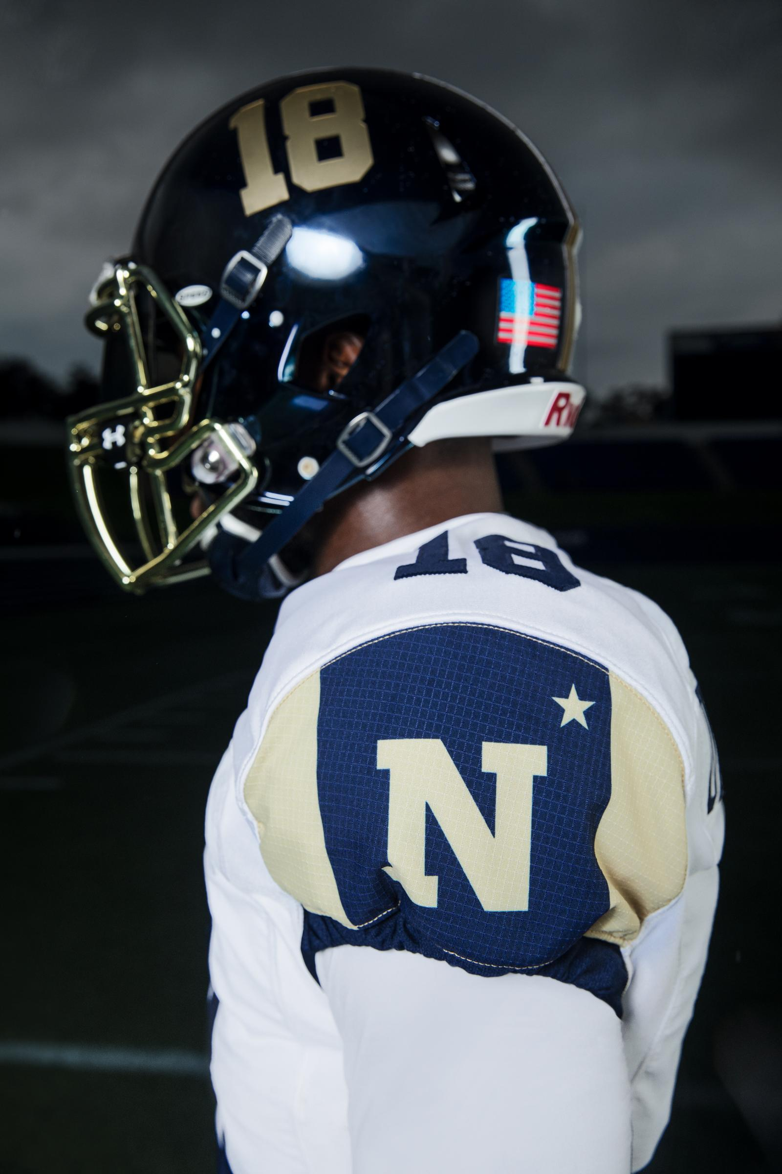 The sleeves of the jersey are navy blue in color and feature two stripes on the outside with the Navy logo in the center. This color-blocking look was inspired directly from the trim of the blanket popularly worn by Bill the Goat.   Bill the Goat is depicted on the sides of the helmet, charging forward and wrapped in its blanket.