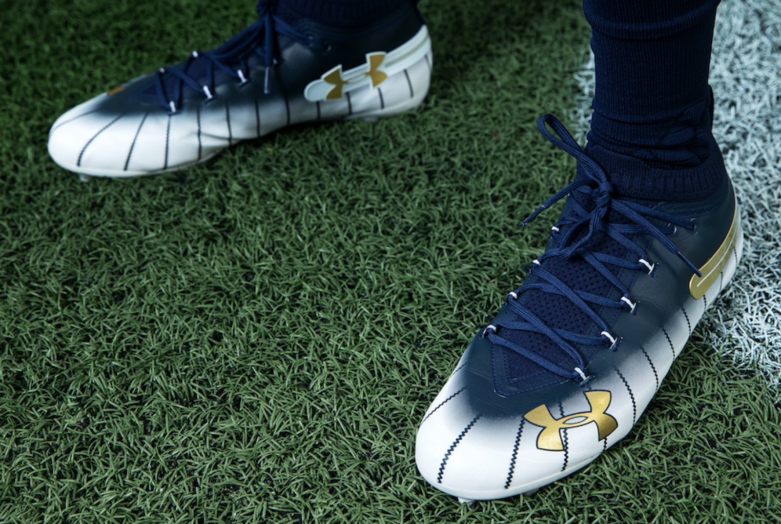 A gold UA logo pops from the front of the cleats aa5e1900a