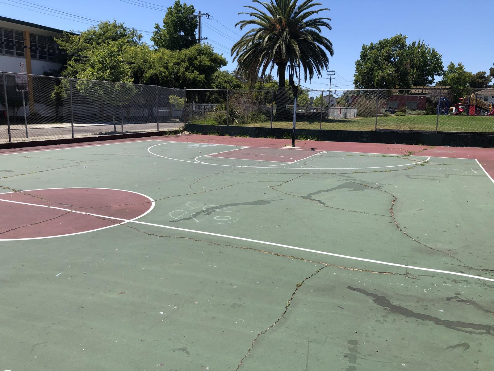 'Before' photo of the Concordia Park basketball court with missing hoop, uneven and cracked pavement.