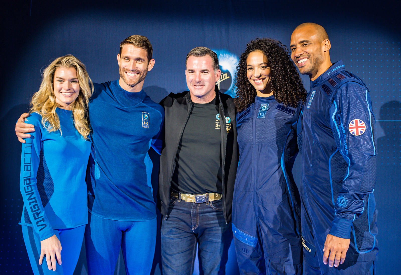 Under Armour Founder Kevin Plank stand with models wearing the UA-designed base layer and spacesuit.